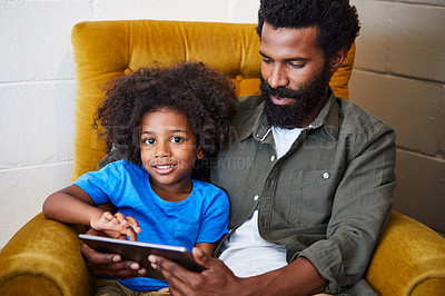Buy stock photo Portrait of a cheerful young father and son relaxing on a chair while browsing on a digital tablet at home