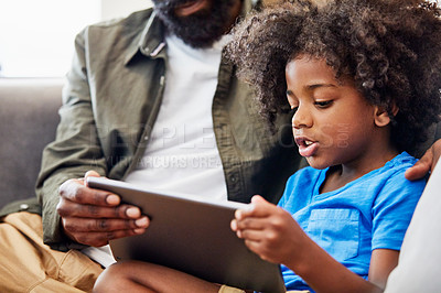 Buy stock photo Shot of a cheerful young father and son relaxing on a chair while browsing on a digital tablet at home