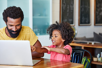 Buy stock photo Shot of a cheerful young father and son browsing on a digital tablet together while being seated at a table in their home