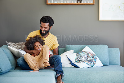 Buy stock photo Shot of a cheerful young father and son relaxing on a couch at home during the day