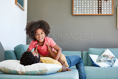 Buy stock photo Portrait of a cheerful little boy being held by his dad while lying down on a couch
