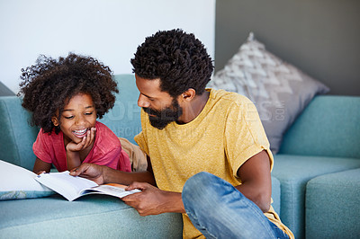 Buy stock photo Shot of a cheerful young father and son reading a storybook while being seated on a couch at home
