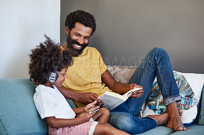 Buy stock photo Shot of a cheerful father and son listening to music and reading a book while relaxing on a couch at home