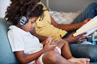 Buy stock photo Shot of a focused father and son listening to music and reading a book while relaxing on a couch at home