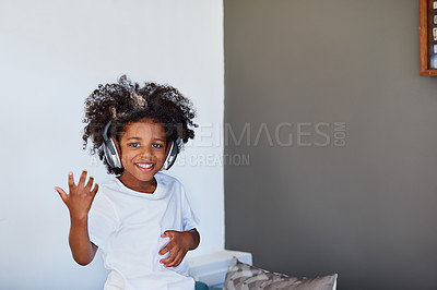 Buy stock photo Portrait of a cheerful young little boy dancing on a couch while listening to music at home during the day