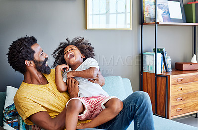 Buy stock photo Shot of a cheerful young man holding his son and ticking him while being seated on a couch at home