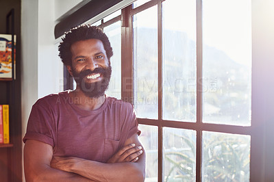 Buy stock photo Portrait of a cheerful young man standing next to a window with his arms folded inside at home during the day