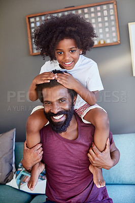 Buy stock photo Portrait of a cheerful little boy sitting on his dad's shoulders with his hands on his dad's head inside at home during the day
