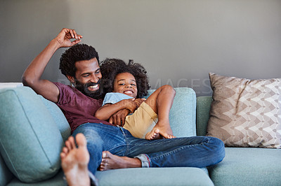 Buy stock photo Shot of a cheerful father and son lying down and relaxing on the couch at home during the day