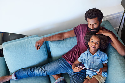 Buy stock photo High angle shot of a cheerful young father and son browsing on a digital tablet while relaxing on a couch at home during the day