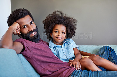 Buy stock photo Portrait of a cheerful father and son lying down and relaxing on the couch at home during the day