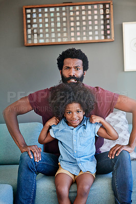 Buy stock photo Portrait of a cheerful father and son flexing their muscles while being seated on a couch at home during the day