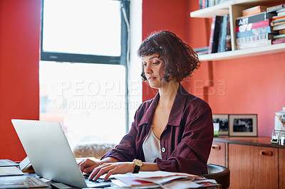 Buy stock photo Cropped shot of a young woman sitting behind her laptop in the office