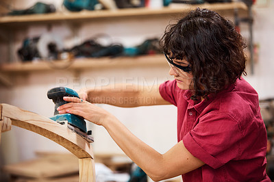 Buy stock photo Shot of a woman working with wood in a furniture manufacturing workshop