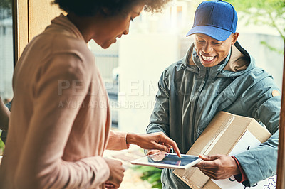 Buy stock photo Shot of a woman using a digital tablet to sign for her delivery from the courier