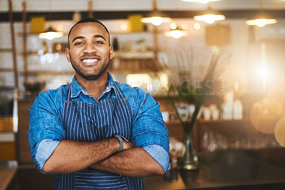 Buy stock photo Cropped portrait of a handsome young man standing with his arms folded in his coffee shop