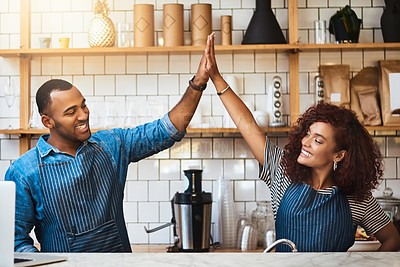 Buy stock photo Cropped shot of an affectionate young couple high fiving while standing in their coffee shop