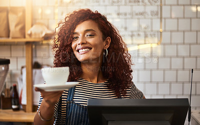 Buy stock photo Shot of a young barista holding a cup of coffee in a cafe