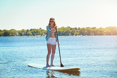 Buy stock photo Shot of an attractive young woman paddle boarding on a lake