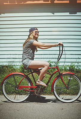Buy stock photo Shot of an attractive young woman riding a bicycle outdoors