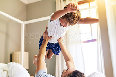 Buy stock photo Shot of a cheerful little boy being picked up by his father while playing around at home in the morning