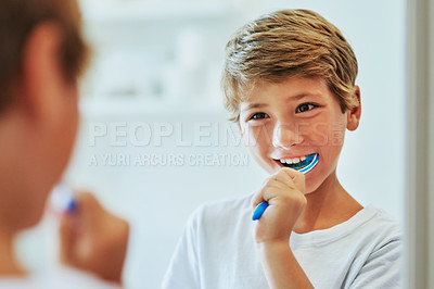 Buy stock photo Shot of a cheerful young boy looking at his reflection in a mirror while brushing his teeth in the bathroom at home during the day