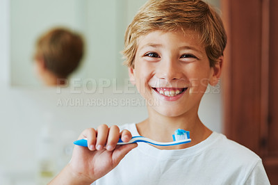 Buy stock photo Portrait of a cheerful young boy looking at his reflection in a mirror while brushing his teeth in the bathroom at home during the day