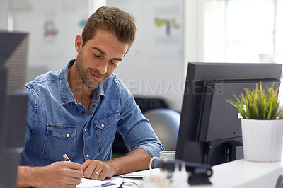 Buy stock photo Cropped shot of a businessman making notes at his desk