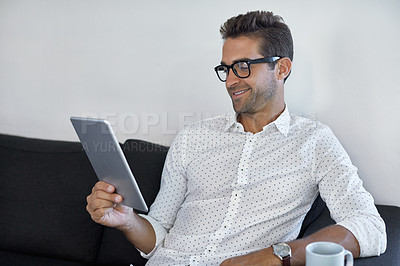 Buy stock photo Cropped shot of a handsome businessman using his digital tablet at work