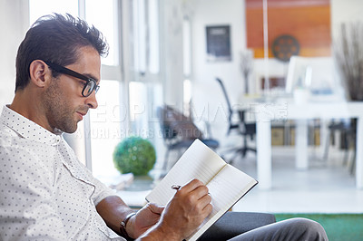 Buy stock photo Cropped shot of a businessman making notes in his diary