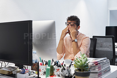 Buy stock photo Cropped shot of a businessman looking stressed while sitting at his desk