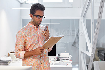 Buy stock photo Cropped shot of a businessman talking on his phone while working on some paperwork
