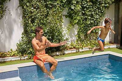 Buy stock photo Shot of a father watching his son dive into the swimming pool