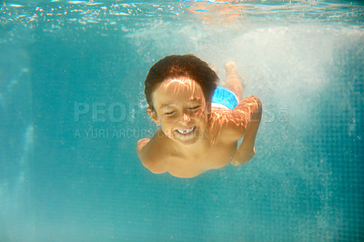 Buy stock photo Underwater shot of a little boy swimming in a pool