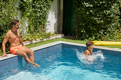 Buy stock photo Shot of a father and his son enjoying a day by the swimming pool