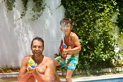 Buy stock photo Portrait of a father and his son playing with water guns at the swimming pool