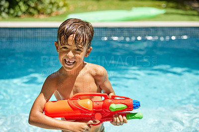 Buy stock photo Portrait of a little boy playing with a water gun in a swimming pool
