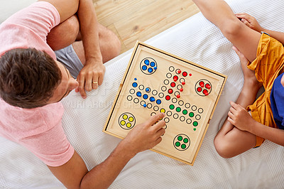 Buy stock photo High angle shot of a father and son playing a board game in the living room at home