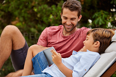 Buy stock photo Shot of a father and son using a digital tablet while relaxing together outside