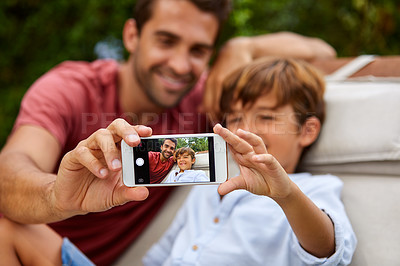 Buy stock photo Shot of a father an son taking a selfie together outside