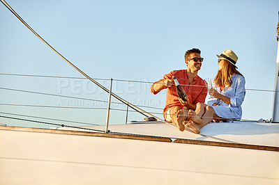 Buy stock photo Shot of a young couple drinking champagne together on an ocean cruise