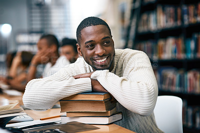 Buy stock photo Shot of a young man resting on a pile of books in a college library and looking thoughtful