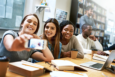 Buy stock photo Shot of a group of young women taking a selfie together while studying in a college library