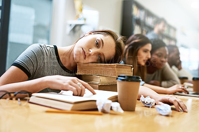 Buy stock photo Portrait of a young woman looking tired while studying in a college library
