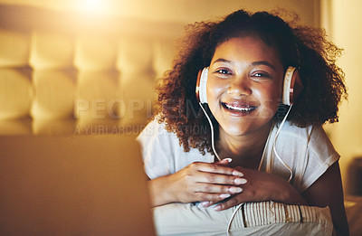 Buy stock photo Portrait of a young woman wearing headphones while using a laptop at home