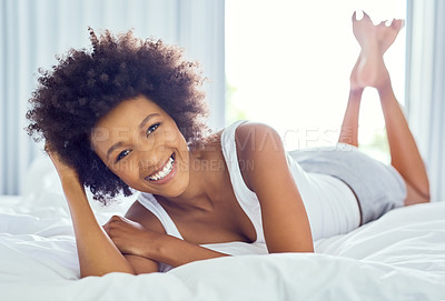 Buy stock photo Shot of an attractive young woman chilling on her bed at home