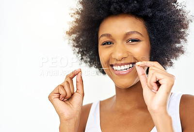 Buy stock photo Cropped shot of an attractive young woman flossing in the bathroom at home