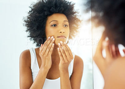 Buy stock photo Cropped shot of an attractive young woman checking her skin in front of a mirror in the bathroom at home