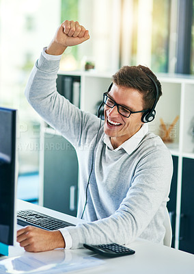 Buy stock photo Shot of a young call centre agent cheering while working in an office