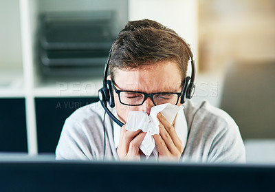 Buy stock photo Shot of a young call centre agent blowing his nose while working in an office